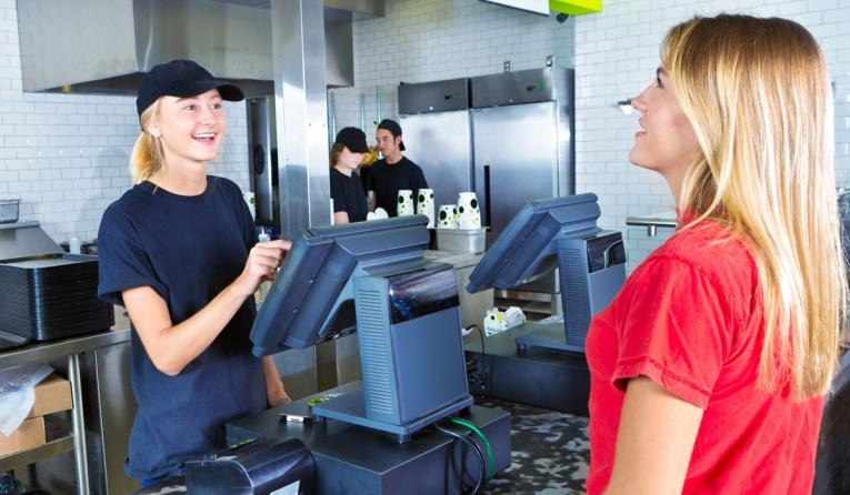 A restaurant employee at a fast-food register helps a customer.