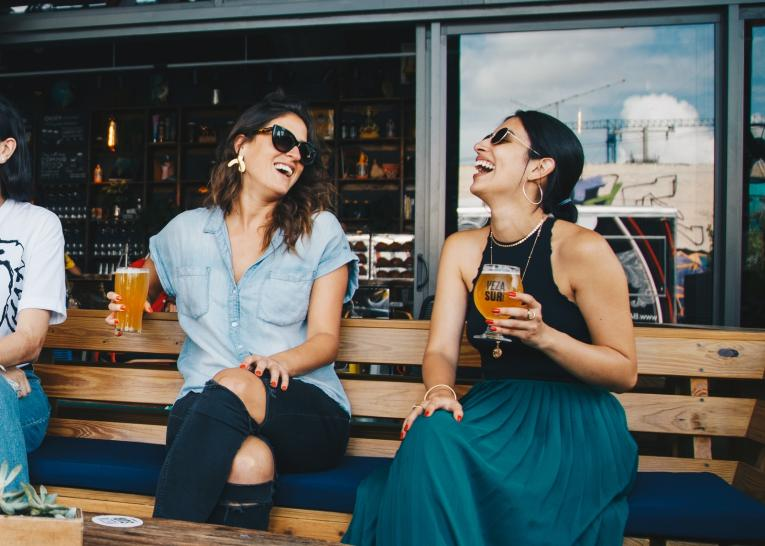 Two women share a laugh as they enjoy a beer.