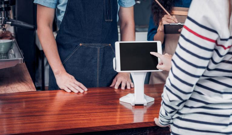 Customer using a tablet to pay for their restaurant bill.