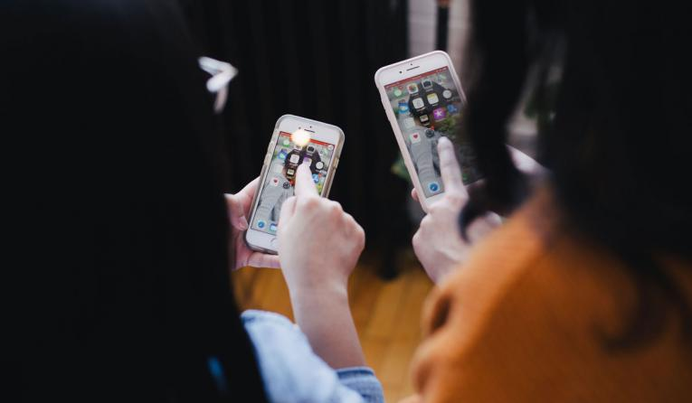 Two women operating smartphones.