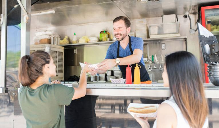 A food truck owner hands food to guests.