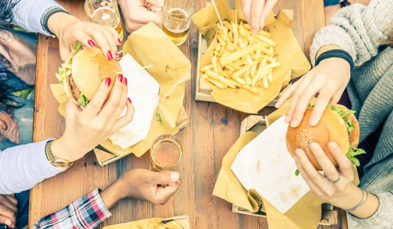 Friends gather around and eat burgers and fries.