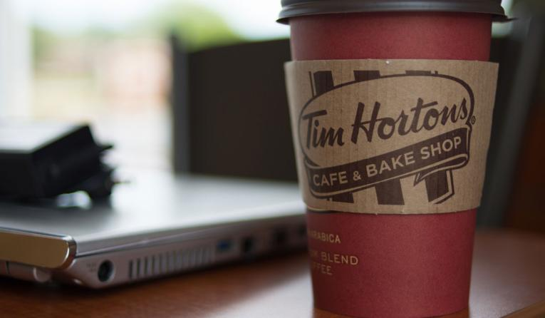 A cup of Tim Hortons coffee next to a computer.