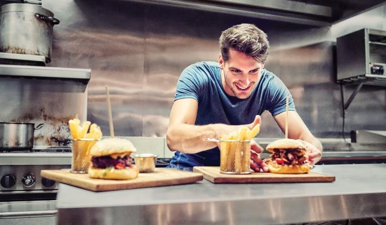A restaurant employee plates a burger.