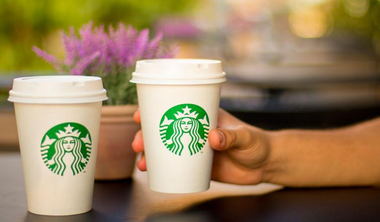 A hand extends to hold two Starbucks coffee cups.