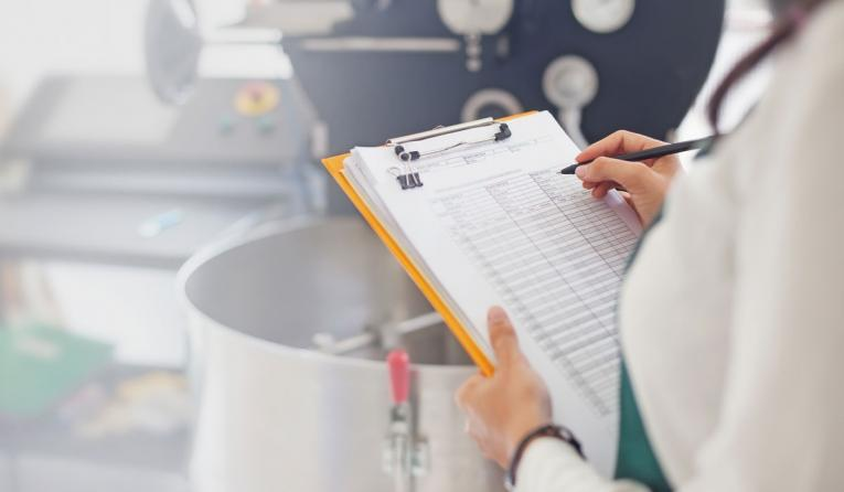 A restaurant worker holds a clipboard with a checklist on it.