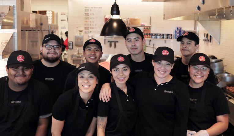 Chipotle employees pose for a picture.