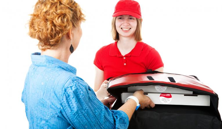 A woman holds open a pizza delivery box for a customer.