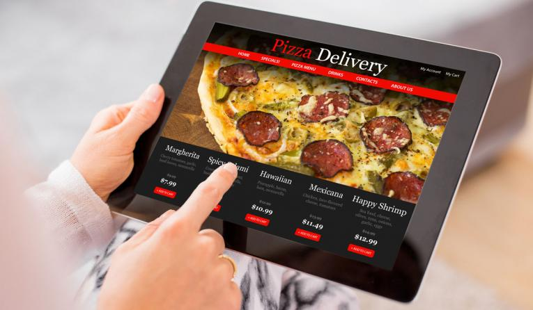 A customer orders pizza from a tablet device.