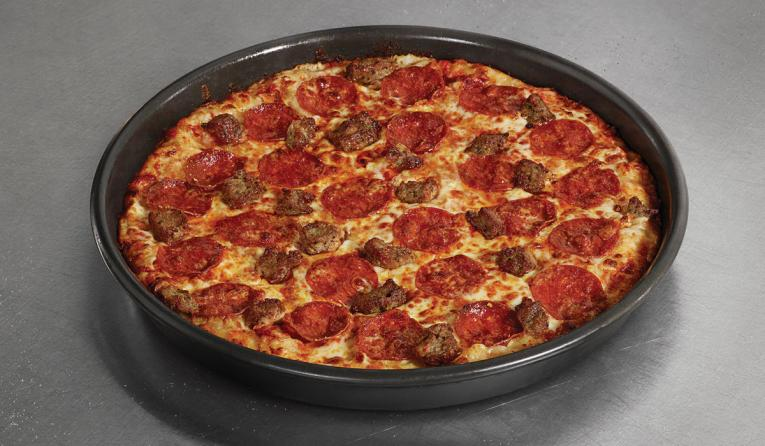 A sausage and pepperoni pizza at Domino's in a black pan.