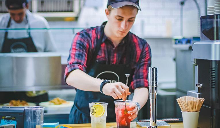 A restaurant worker mixes a drink.