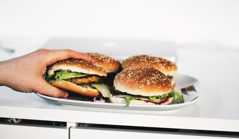 Person holding hamburger on plate.