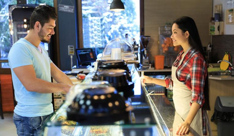 A restaurant worker chats with a guest over the counter.