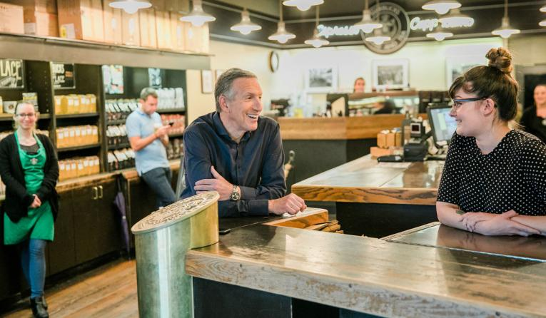 Starbucks leader Howard Schultz talks with a customer.