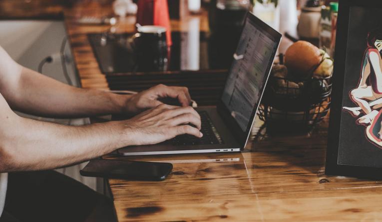 A man types on a laptop at a restaurant.