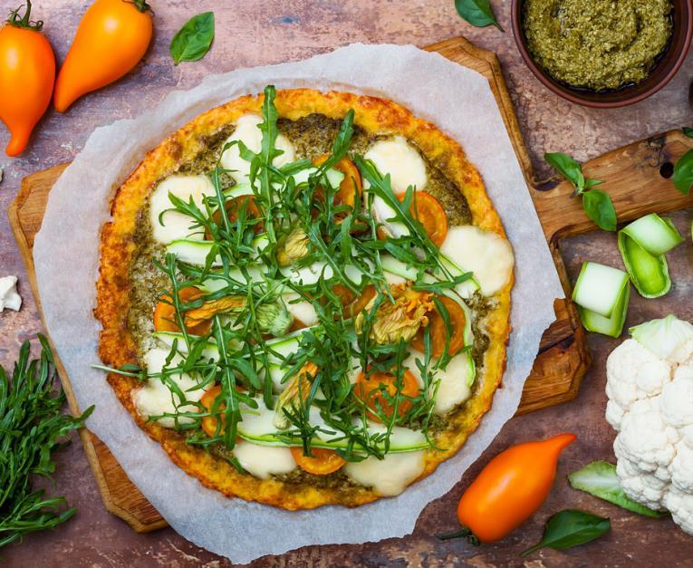 Cauliflower pizza crust with pesto, yellow tomatoes, zucchini, mozzarella cheese and squash blossom