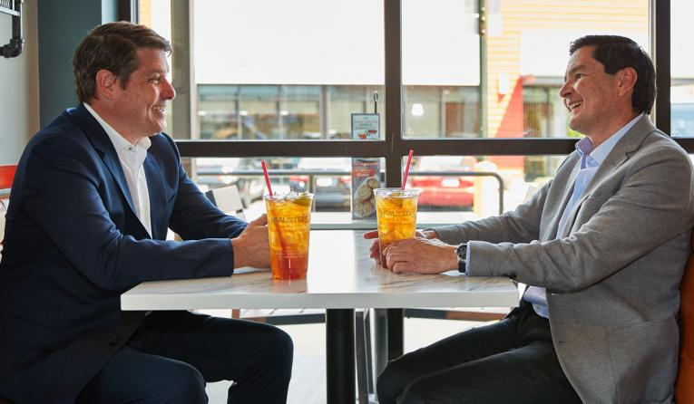 Sun Holdings franchise group CEO and president Guillermo Perales (right, seen talking with McAlister's Deli president Joe Guith) recently acquired 98 McAlister's units.
