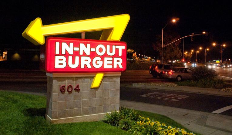 In-N-Out Burger's famed arrow sign outside a restaurant at night.