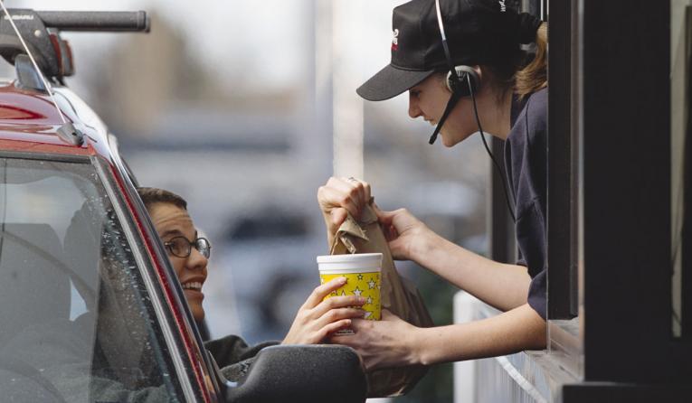 A drive-thru worker hands a customer their food.
