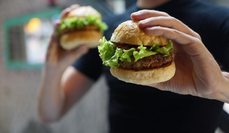 A man holds two burgers out front.