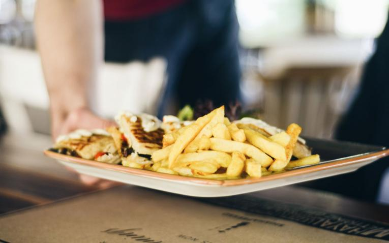 A fast-food worker brings a tray of fries to a table.