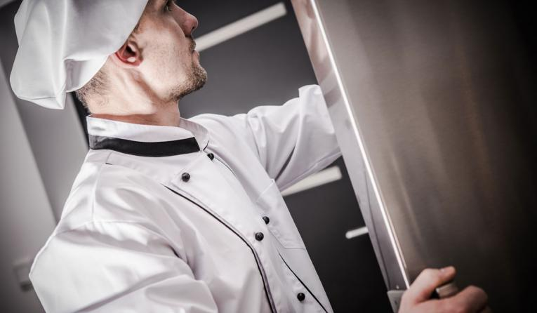 A chef opens the refrigerator in his restaurant.