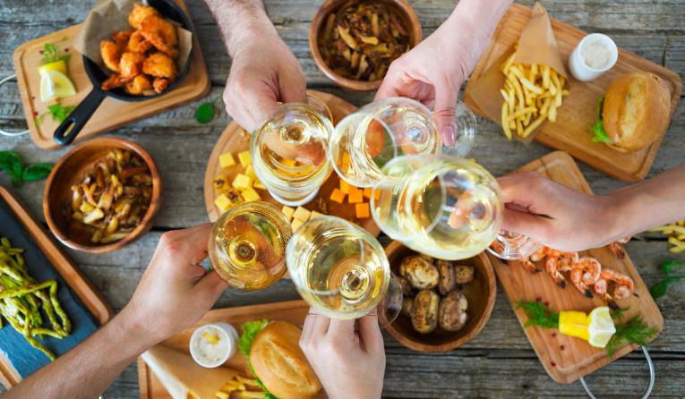 Restaurant guests cheers with wine while eating a meal.