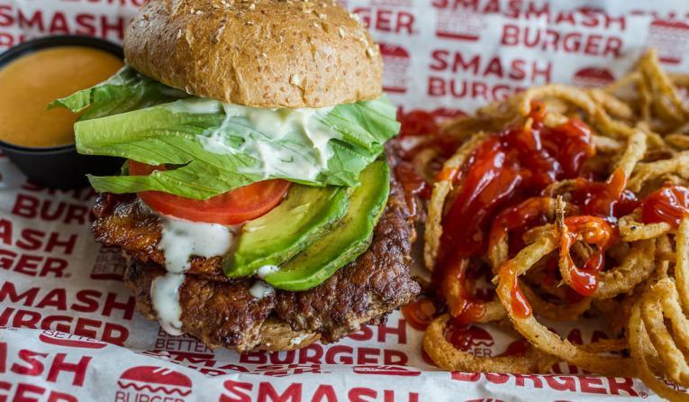 Burger with avocado and fries at Smashburger.