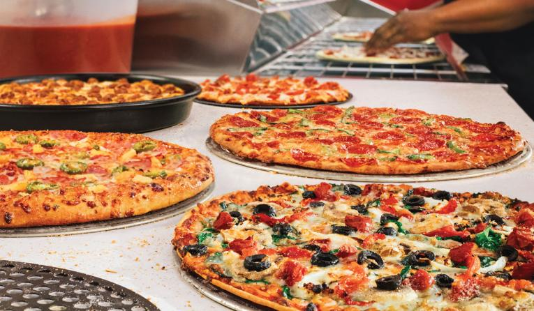 Five Domino's pizzas on a table.