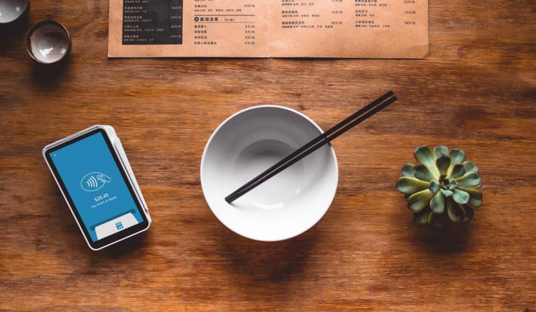 Black chopsticks in white ceramic bowl on table.