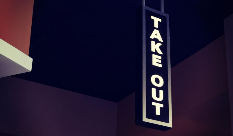 A take-out sign in front of a restaurant.
