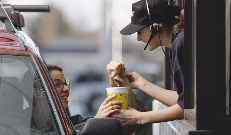 A restaurant employee hands a customer food through a drive-thru window.