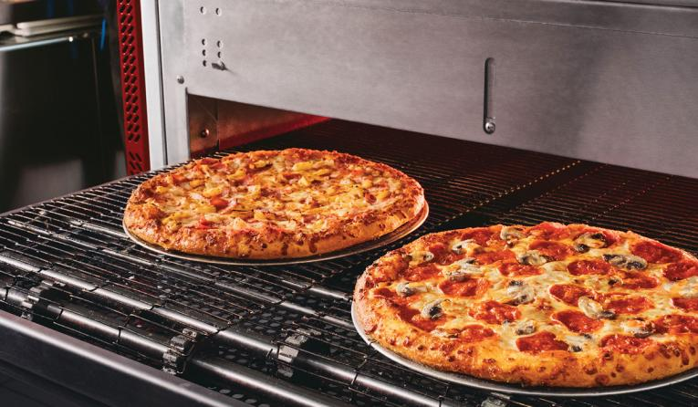 Two pizzas being loaded into the oven at Domino's.