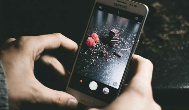 A customer holds a phone to take a picture of dessert.