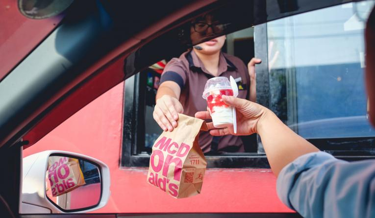 McDonald's worker hands food to a customer at the drive thru.
