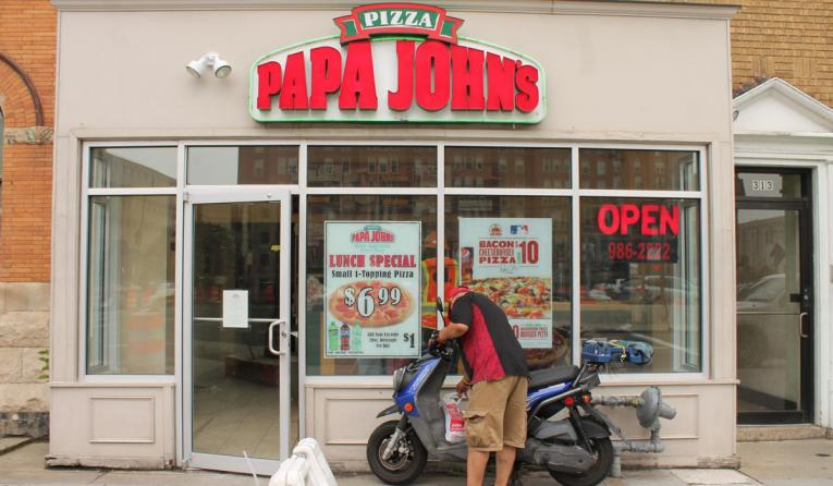 Papa John's restaurant with a delivery driver out front.