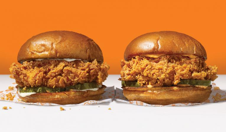 Popeyes' chicken sandwiches side by side against an orange background.