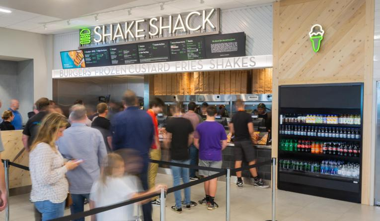 Customers line up at a Shake Shack airport location.