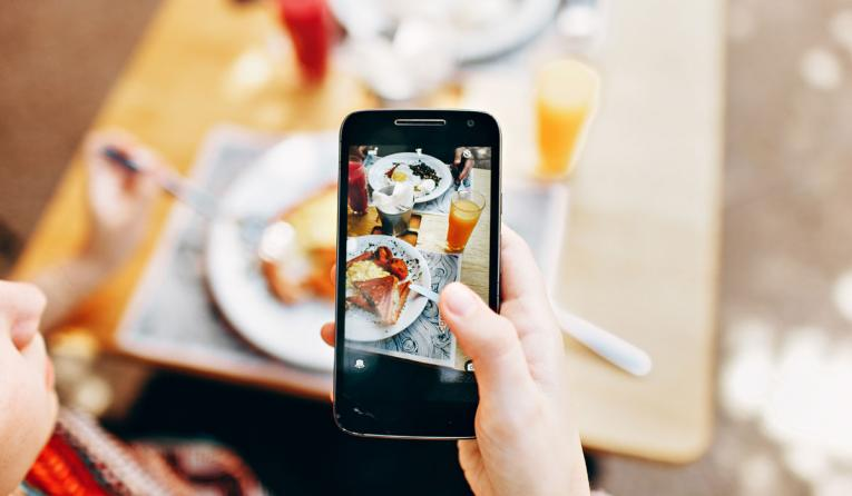 A person holds up a phone taking a picture of food.