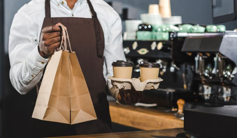 A man hold a bag of food and coffee out to a customer.