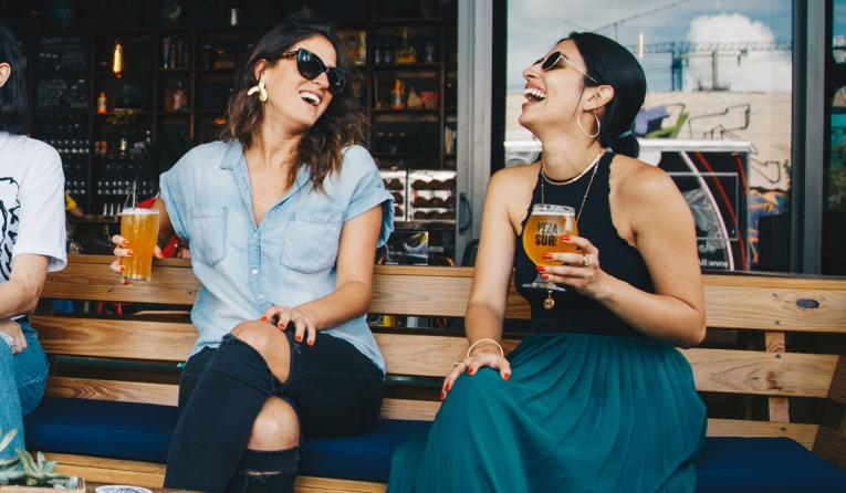 Two women drink beer outside a restaurant.