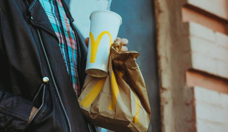 A customer holds a McDonald's bag and drink.