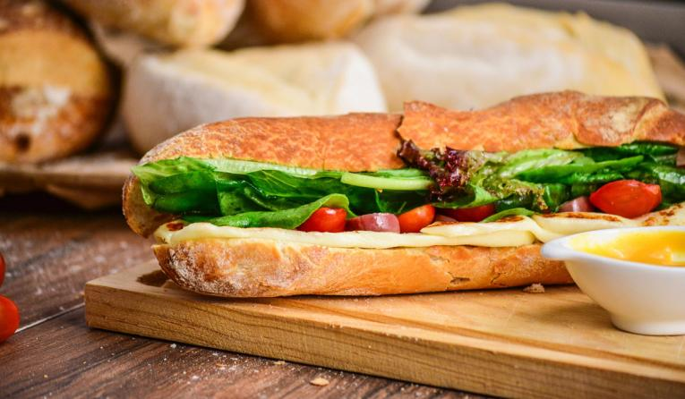 Baked bread with vegetables on brown chopping board.
