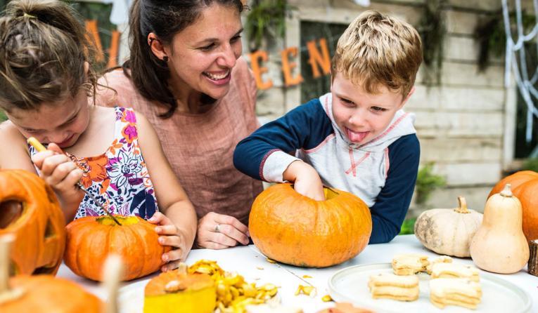 A parent carves pumpkin with her kids.