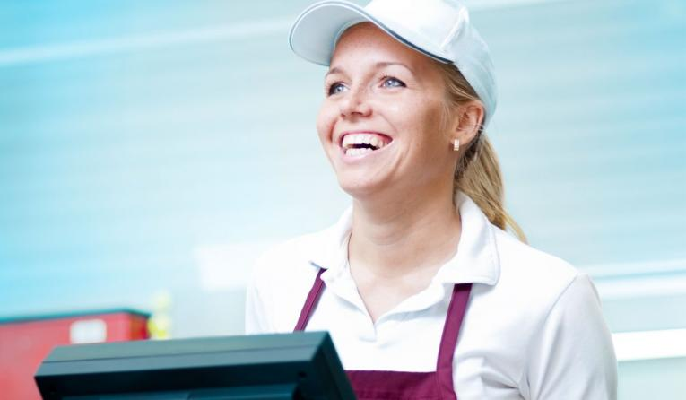 A restaurant worker stands behind the point-of-sale system, smiling.