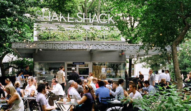Shake Shack location surrounded by trees in New York City.