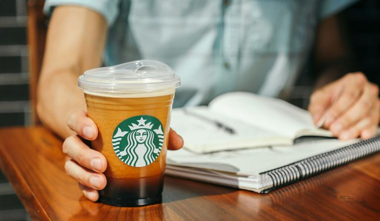 A Starbucks customer holds a cup with a strawless lid.