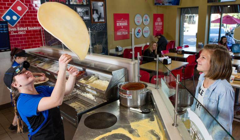 Domino's employee tosses pizza dough in the air.