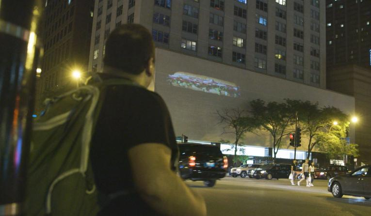 A customer looks at a Subway sandwich on a building.