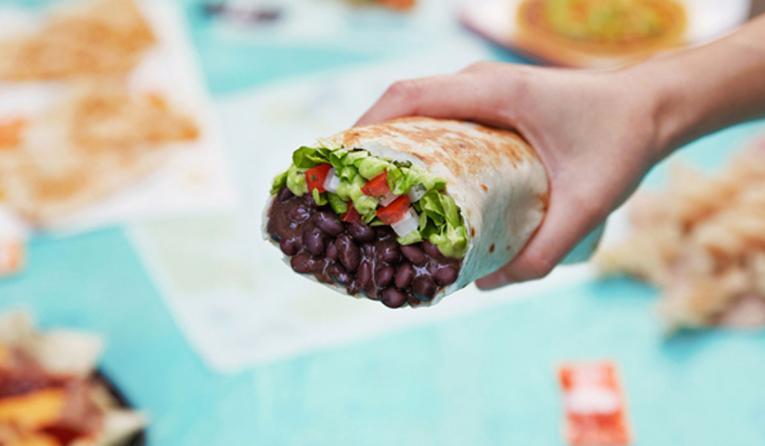 A hand holds Taco Bell's Power Menu Burrito.